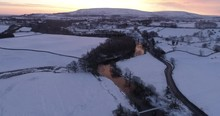 Aerial Shot Of Colorful Sunrise In The Snow Covered Valley.
