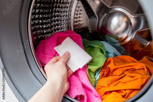 Woman hand put color absorbing sheet inside a washing machine, allows to wash mixed color clothes without ruining colors concept Canvas Print