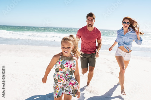 Obraz Young happy family running on beach - fototapety do salonu