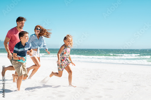 Obraz Happy family running on beach - fototapety do salonu
