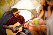 Hipster Man With Guitar On Camping Trip