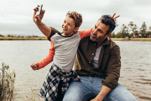 Fotografía  Father and son having fun taking selfie outdoors