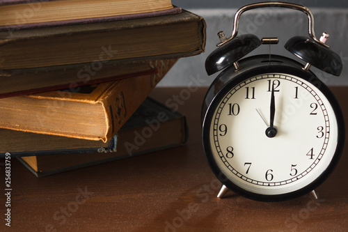 Fotografía  piles of different old books on a dusty table and an alarm clock
