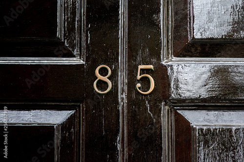 Cuadros en Lienzo House number eighty five with the 85 in bronze lettering on a black wooden paint