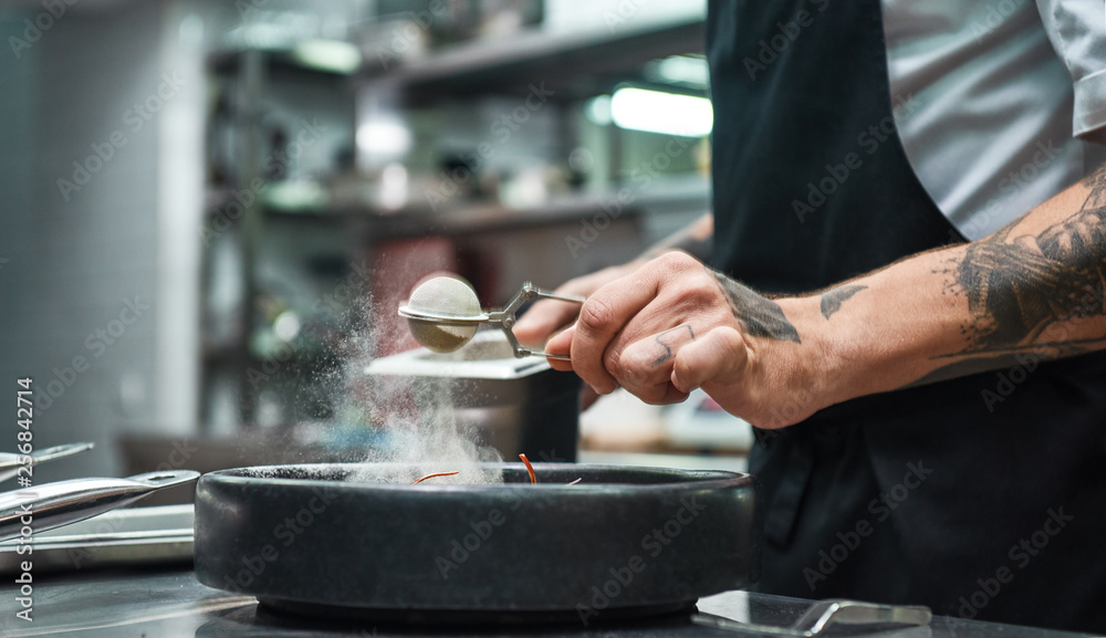 Fototapety, obrazy: Slow motion. Cropped image of restaurant chef hands with several tattoos adding a spice to fresh cooked pasta Carbonara.