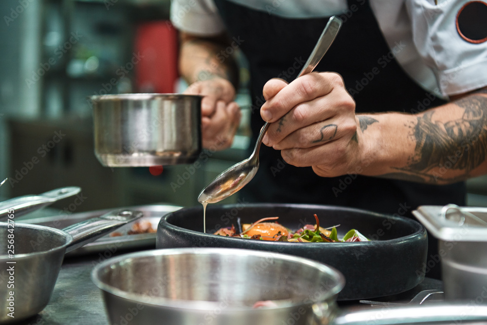 Fototapety, obrazy: Secret recipe. Close up photo of chef hands with several tattoos adding a sauce to italian pasta Carbonara.