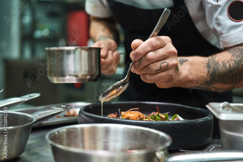 Fototapeta Secret recipe. Close up photo of chef hands with several tattoos adding a sauce to italian pasta Carbonara. obraz
