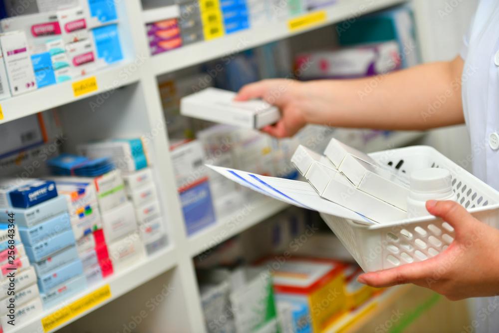 Fototapety, obrazy: Pharmacist filling prescription in pharmacy drugstore