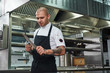Everything should be perfect Brutal chef with several tattoos on his arms sharpening a knife while standing in a restaurant kitchen