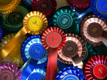 Pile Of Real Rosettes Badges With First, Second Third And Fourth In The Centre