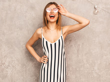 Portrait Of Young Beautiful Smiling Hipster Girl In Trendy Summer Zebra Dress. Sexy Carefree Woman Posing Near Gray Wall. Positive Model Having Fun In Round Sunglasses
