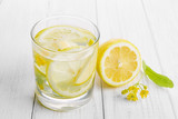 Refreshing drink for health, lemon water in a glass and yellow linden flowers on a white table.