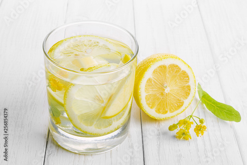 Photographie Refreshing drink for health, lemon water in a glass and yellow linden flowers on a white table
