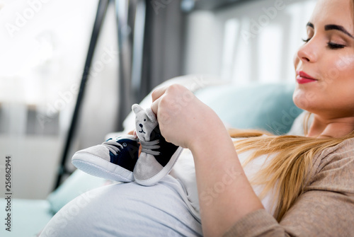 Canvas Print Young pregnant woman with small baby shoes sitting on sofa at home, child expect