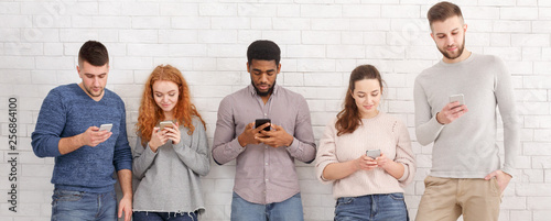 Fotografie, Obraz  Gadget addiction. Group of students with smartphones