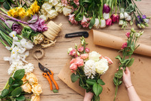 Partial View Of Florist Making Flower Bouquet On Wooden Surface