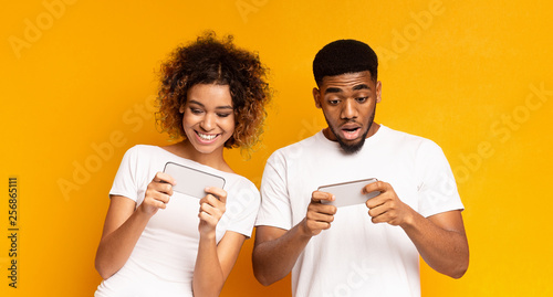 Fotografie, Obraz  Emotional african-american man and woman watching videos online