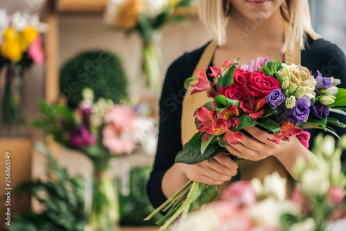 Cropped view of florist in apron holding bouquet in flower shop