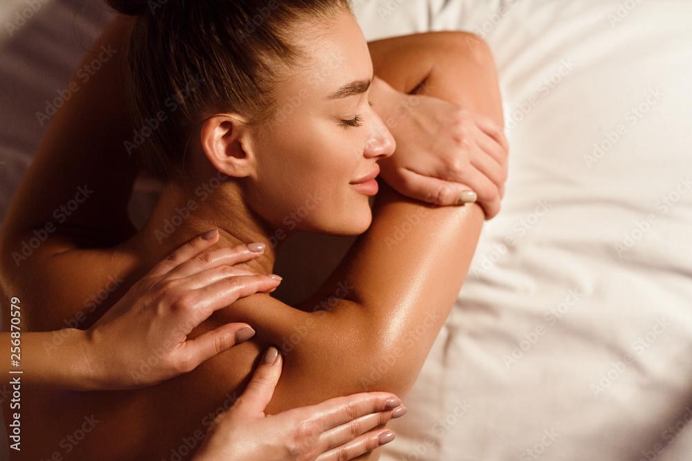Fototapeta Woman enjoying shoulder massage in spa salon
