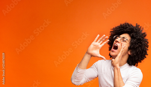 Fotografía  Emotional black guy screaming on orange panorama background