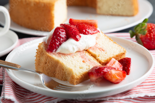 Photo Angel food cake with whipped cream and strawberries
