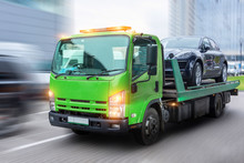 Passenger Car Loaded Onto A Tow Truck For Transportation, Delivered To The Destination. With Motion Blur Speed Effect.