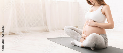 Active pregnant woman sitting on floor after doing sports Wallpaper Mural
