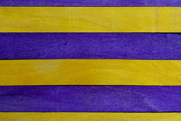 Beautiful texture of natural wood slats of yellow and purple colors. Natural and aged appearance.