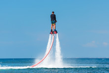 Water Extreme Sport. The Guy Is Flying At The Aquatic Flyboard. Extreme Rest On The Sea. A Lot Of Water Pressure.