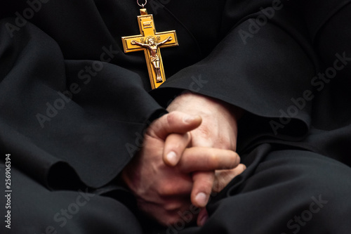 Golden cross with crucifixion of Jesus on the chest of a priest in black clothes Wallpaper Mural