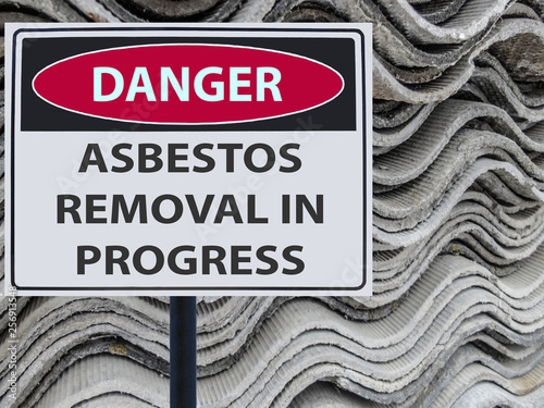 Photo sign danger asbestos removal in progress and a stack of sheets roof of asbestos