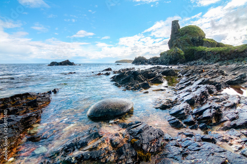 Obraz na plátně Jagged rock layers and boulders smoothed by the ocean are seen at an intertidal zone on the island of Islay, Scotland, UK