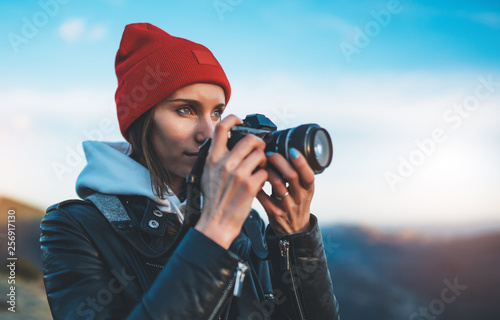 Fototapeta hipster tourist girl hold in hands take photography click on modern photo camera, photographer look on camera technology, journey landscape vacation concept, sun flare mountain obraz na płótnie