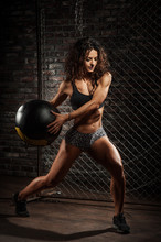 Female Fitness Model Exercising With Medicine Ball At Studio Gym. Young Caucasian Woman Doing Crossfit Workout.
