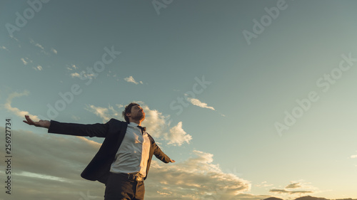 Canvas Print Young businessman relaxing under evening sky