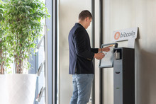 Young Businessman Buying Cryptocurrency On ATM Machine For Buying And Selling Cryptocurrency.
