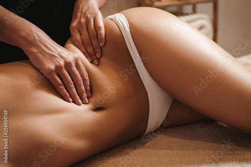 Poster Spa Anti cellulite belly massage for young woman in beauty salon. Perfect skin fat burning beauty concept