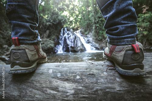 Crédence de cuisine en verre imprimé Rivière de la forêt Close up shoes of traveler standing in front waterfall. hiking concept.
