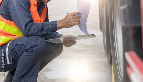 Fotografie, Obraz Preforming a pre-trip inspection on a truck,Concept preventive maintenance truck checklist,Truck driver holding clipboard with checking of truck