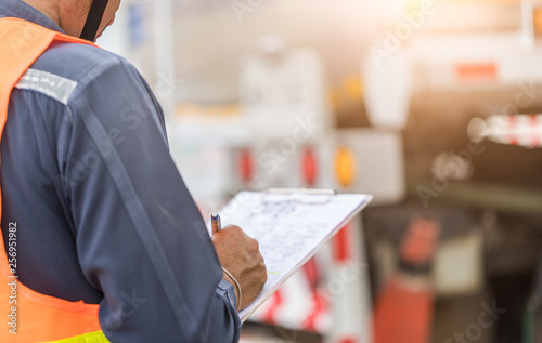 Foto Preforming a pre-trip inspection on a truck,Concept preventive maintenance truck checklist,Truck driver holding clipboard with checking of truck,spot focus