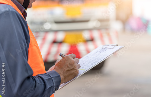 Fotografiet Preforming a pre-trip inspection on a truck,Concept preventive maintenance truck checklist,Truck driver holding clipboard with checking of truck,spot focus