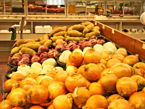 Fotografie, Obraz  Fresh onions and potatoes for sale on shelves in grocery store.