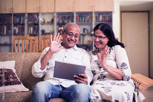 Fotografie, Obraz Indian/asian Senior couple video chatting on tablet/computer while sitting at co