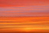The sunset or sunrise. The cloudy sky cloured in red, orange, rose, scarlet, crimson, purple, violet and blue bright and vivid coloures with setting or rising sun in the evening or in the morning