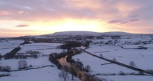 Aerial Shot Of Dramatic Sunrise Over A Snow Covered Valley.