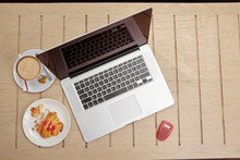 Laptop And Snack On Cafe's Table