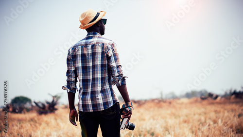Fotografie, Obraz  African man photographer holding camera on a dry field.16:9 style