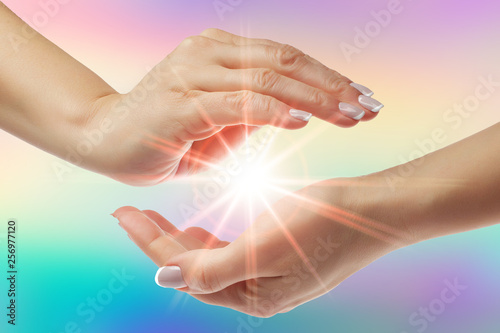 Fotografia, Obraz Healing hands with bright sunburst on rainbow background
