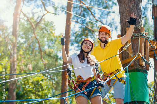 Young woman and man in protective gear are standing on rope bridge hanging on high trees, posing and smiling. Rope park with obstacles and ziplines. Extreme rest and summer activities concept.