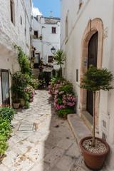 Fototapeta na wymiar Walking in Locorotondo. Narrow streets and white houses. Dreamlike Puglia, Italy